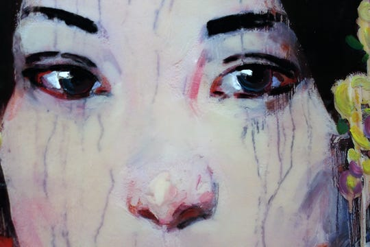 "A detail of the eyes in""Red Wash Edition,"" a 2014 mixed media on panel by Hung Liu, on exhibit at The Grace Museum."