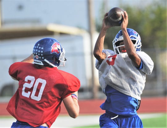 Cooper receiver Izaiah Clark, right, makes a catch as teammate Brady Miller (20) defends during the Cougars' practice Monday, Sept. 30, 2019, at Cooper High School. The play went for a TD.