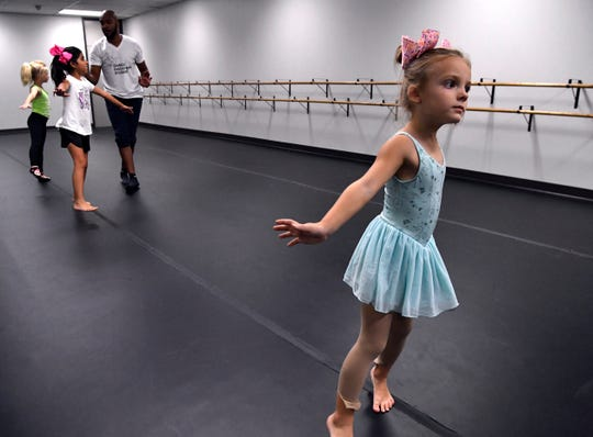 Henley Gibbs twirls across the room as instructor Domonique Gordon assists another one of his students at Dance Discovery Studios Sept. 25, 2019. The dance school, which was devastated by a tornado May 19, has a new home with more room just a few blocks from its former location.