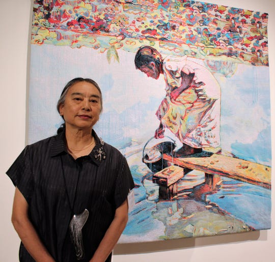 "Chinese-American artist Hung Liu with one of her 19 works on display as part of her show titled ""The Long Way Home"" at The Grace Museum."