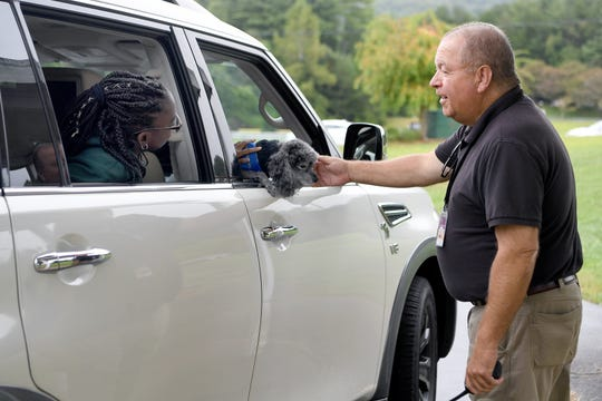 "Mike Ruby chats with Reynolds Middle School eighth-grader Jade Stephens, 13, as he pets her dog, Smoke, while she waits in the car line at the school on Aug. 27, 2019. ""It's all about the relationships that you make,"" Ruby said about his time leading the unit of School Resource Officers with the Buncombe County Sheriff's Department."
