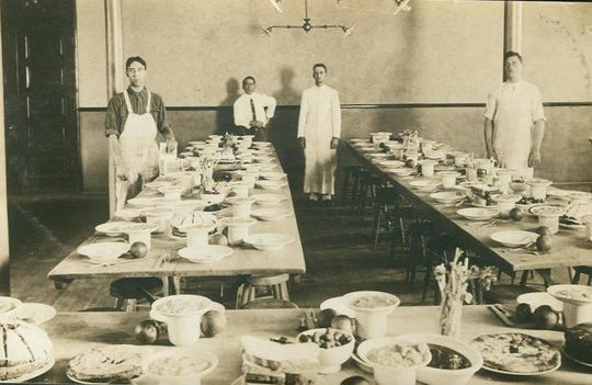 An undated postcard showing a photograph of men standing with food and tables set for a meal, believed to be a dining room for staff at the Battle Creek Sanitarium.