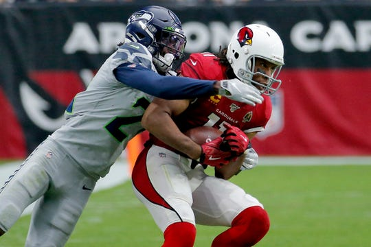 Arizona Cardinals wide receiver Larry Fitzgerald pulls in a catch as Seattle Seahawks cornerback Tre Flowers  defends Sunday, Sept. 29, 2019, in Glendale, Ariz.