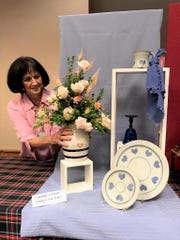 "Mary Lee Minor places a completed, fresh floral design on a table picture for ""Grandma's Kitchen"" during a recent school for flower show exhibitors and judges. Her lecture portion covered winter and holiday flower shows for the Ohio Association of Garden Clubs."
