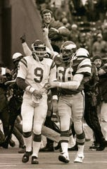 Philadelphia Eagles linebacker BIll Bergey (66) consoles Minnesota Vikings quarterback Tommy Kramer (9) as Eagles coach Dick Vermeil gest a happy victory ride after the Eagles beat the Vikings 31-16 in the NFC playoff game in this Jan. 5, 1981 file photo, in Philadelphia.(AP Photo/Rusty Kennedy)