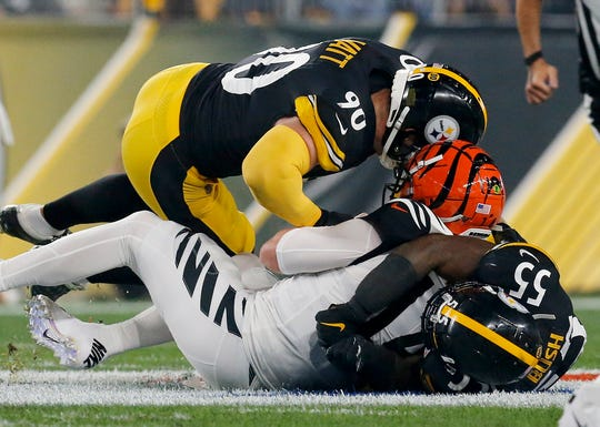 Cincinnati Bengals quarterback Andy Dalton (14) is sacked by Pittsburgh Steelers linebacker Devin Bush (55) and outside linebacker T.J. Watt (90) in the first quarter of the NFL Week 4 game between the Pittsburgh Steelers and the Cincinnati Bengals at Heinz Field in Pittsburgh on Monday, Sept. 30, 2019.
