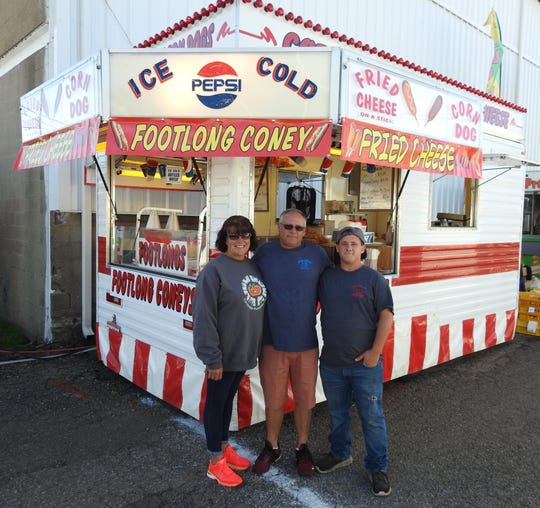 Jenny, Bobby and Michael Endsley stand in front of their food concession stand near the grandstand on the midway of the Coshocton County Fair. Bobby is originally from Walhonding and is the fifth generation of his family in the business. Jenny is the third generation of her family and they hope Michael and their other children might follow in their footsteps.