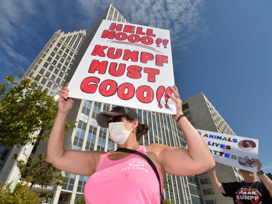 A volunteer, who would not give her name fearing reprisal, protests in front of the Coleman A. Young Municipal Center.