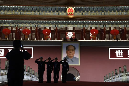 Chinese security personnel pose for photos in front of Mao Zedong's portrait on Tiananmen Gate after an evening gala held on Tiananmen Square for the 70th anniversary of the founding of the People's Republic of China in Beijing on Tuesday, Oct. 1, 2019.