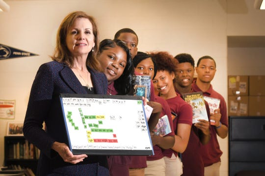 Michiganian of the Year Pamela Good, founder of Beyond Basics, a nonprofit organization that's dedicated to fighting illiteracy, poses with program students at Mumford High School in Detroit on Thursday, September 12, 2019.