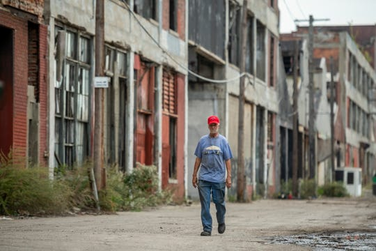 Allan Hill walks between the buildings of the Packard Plant on Bellevue St. in Detroit, October 1, 2019. Hill has been told to vacate the warehouse inside the plant that he has used as a residence and for storage for 15 years.