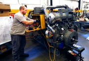 In this Sept. 18, 2019, photo technician David Boxx works on updating an electrical system on a Caterpillar machine at the Puckett Machinery Company in Flowood, Miss. The Institute for Supply Management, an association of purchasing managers, said Tuesday that its manufacturing index shrank for the second straight month to 47.8% in September.