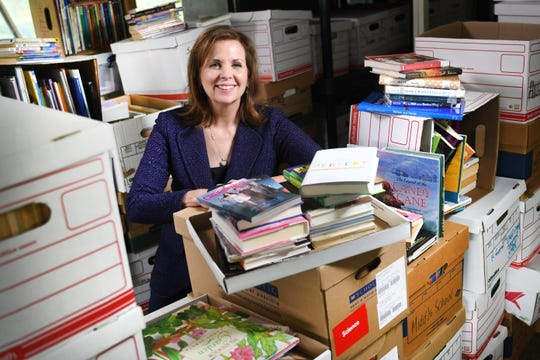 Pamela Good, founder of Beyond Basics, a nonprofit organization that's dedicated to fighting illiteracy among children, is surrounded by donated books at their Southfield offices on Thursday, September 12, 2019.
