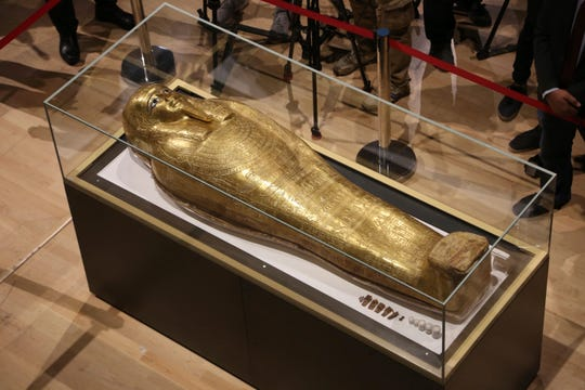 Journalists gather around the golden coffin that once held the mummy of Nedjemankh.