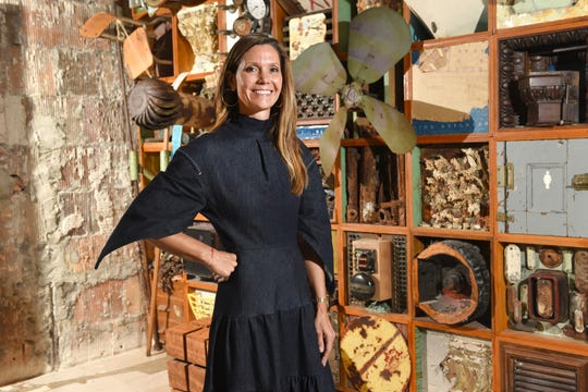 Jennifer Gilbert, wife of Dan Gilbert, is pictured at Pophouse in front of the Relic Wall created by artist Scott Hocking and Clinton Snider on Thursday, September 26, 2019.