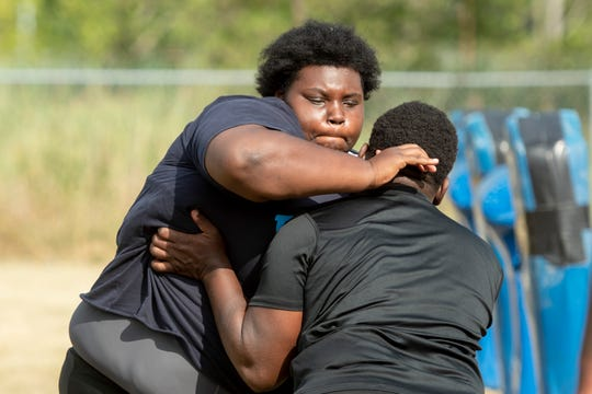 Ecorse high school offensive guard Janay Lakey tries to push her way past a teammate during practice, August 13, 2019.