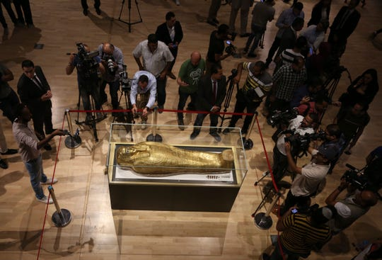 Journalists gather around the golden coffin that once held the mummy of Nedjemankh, a priest in the Ptolemaic Period some 2,000 years ago, at the National Museum of Egyptian Civilization, in Old Cairo, Egypt, Tuesday, Oct. 1, 2019.