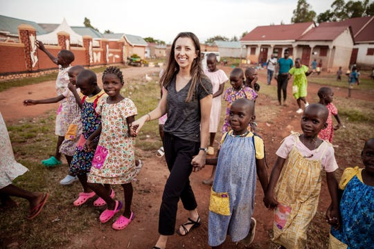 "Ashley Boyd walks with children in Uganda. ""It's such a beautiful place and the people are just the most generous and kind and gracious people you'll ever meet in your whole life,"" she said."