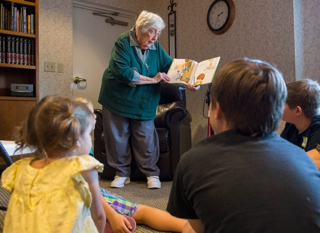 """Resident Janet Wilson, 91, reads """"If You Give a Mouse a Cookie"""" to children during Atria Newburgh's Life Guidance program One Sweet Cookie event in Newburgh, Ind., Tuesday, Oct. 1, 2019."""