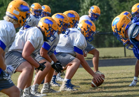 Wren senior Hayden Adams gets ready to snap a ball with teammate offensive linemen during practice in Piedmont Tuesday.