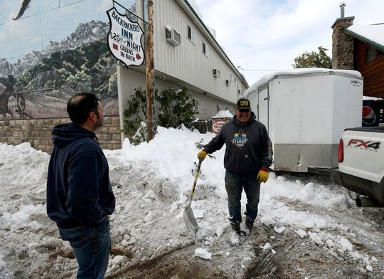Jeff Zarycki, left, owner of Serrano's Mexican Restaurant, and John Ray, owner of the Circle R Motel, talk in East Glacier, Mont., on Monday, Sept. 30, 2019. The town was estimated to have gotten 54 inches of snow over the weekend. (Tom Bauer/The Missoulian via AP)