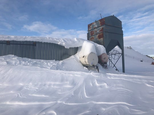 Drifts nearly cover sheds near Heart Butte