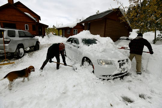 Kellie Miller, left, and her husband, David, shovel out his car at a neighbor's house on Heart Butte Cutoff Road near East Glacier on Monday, Sept. 30, 2019. Residents have been digging out after a storm dumped more than 4 feet of snow in the area over last weekend. (Tom Bauer/The Missoulian via AP)