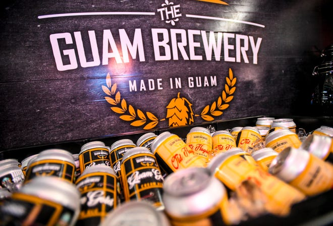 Cans of Guam Gold Creme Ale and Old Hagåtña Honey Rye Ale craft beer chill on ice during a ceremonial ribbon cutting held to celebrate the grand opening of The Guam Brewery in this Oct. 1, 2019, file photo.