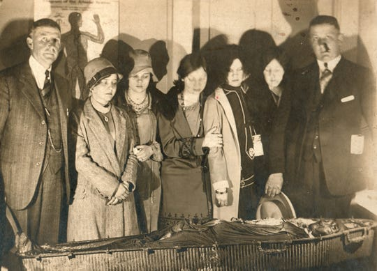 Viewing, at Rudy-Rowland Funeral Home on March 14, 1927, the mysterious corpse found in a coffin floating in the Ohio River are (from left) J.H. Rowland, Mary Frances Lambert, Kate Mason, Kitty L. Hicks, Delorese Brackett, Larraine Posey and Paul B. Moss.
