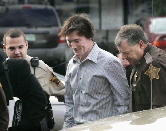 Indianapolis U.S. District Court Judge James Sweeney on Monday vacated a murder conviction against John Myers II, center, who is shown in a 2006 file photo.