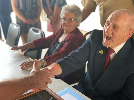 Jimmie H. Royer shakes the hand of a community member who attended the ceremony on Sunday, Sept. 29, at the American Legion in Terre Haute. He was awarded France's Legion of Honor, the country's highest honor, for his service during World War II.