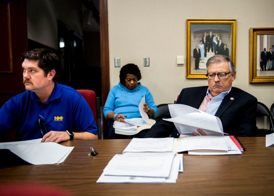 Councilman Russ McKelvey, left, and Councilman Gary Pickens, right, view the agenda before a city council meeting.