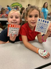 Broadmoor Elementary students Bella Dugas and Audrey Broussard play Book Bingo, where the prizes are new books from Scholastic. The event is a regular fixture at the school aimed at increasing parental involvement. The next Book Bingo night is Oct. 10 forthird- and fourth-graders and their families.