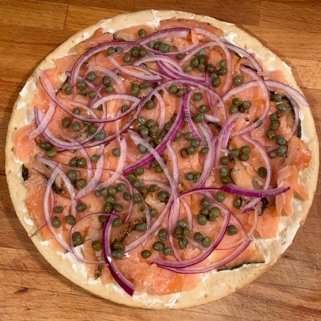 Smoked salmon cauliflower crust pizza with red onions and capers.