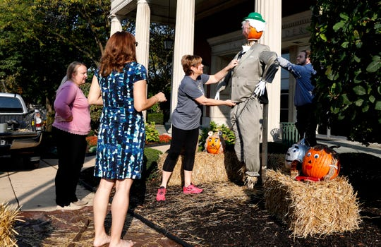 Fairfield Federal employees put the finishing touches on a scarecrow in front of the savings and loan Monday, Sept. 30, 2019, in downtown Lancaster. The scarecrow is part of a trail throughout Fairfield County.