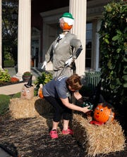 Christa Moody adjusts a pumpkin decorated to be the Wicked Witch of the West in front of Fairfield Federal savings and loan Monday, Sept. 30, 2019, in downtown Lancaster. The scarecrow is part of a trail spread out throughout Fairfield County.