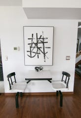 A Japanese artwork, made just for the Morgan's home, shown Tuesday, Oct. 1, 2019, sits over Arby's restaurant dining furniture they repainted to match the black and white theme throughout the house.