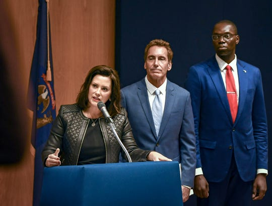 Michigan Gov. Gretchen Whitmer speaks about the state budget Tuesday, Oct. 1, 2019, during a press conference at the State Library and Michigan History Center in Lansing, Michigan.  Also pictured is State Budget Director Chris Kolb, middle, and Lt. Gov. Garlin Gilchrist. [AP Photo/Matthew Dae Smith/Lansing State Journal]