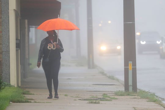 Rachel Barney of Milwaukee uses an umbrella to shield herself from a light rain while walking through the fog along North King Drive near West Locust Street in Milwaukee Monday.
