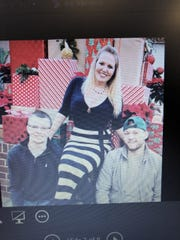 At a September news conference, Kenosha Sheriff's Department officials show a photo of Courtney Huffhines with her sons, Tyler and Jacob.