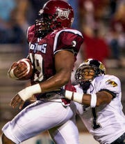 Troy offensive lineman Junior Louissaint (79) drags Missouri defender A.J. Kincade (7) as he scores a second quarter touchdown on Thursday September 9, 2004 in Troy, Ala.