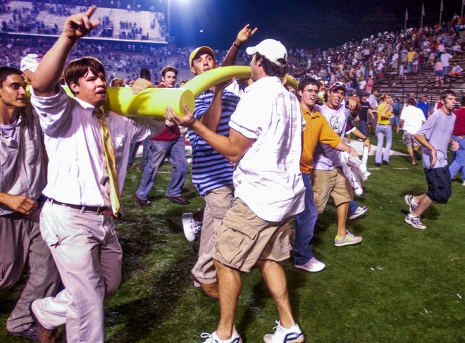 Troy fans parade the goalpost around the field after Troy beat Missouri on Thursday September 9, 2004 in Troy, Ala.