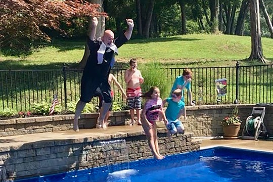 Dressed in his graduation cap and gown, Trey Lee, left, assistant superintendent of engineering and construction for Rutherford County Schools, jumps into a pool during a family reunion to completing his degree.