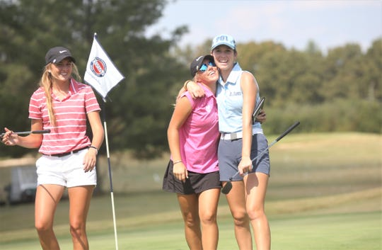 St. Agnes senior Rachel Heck (right) hugs Knox Catholic's Kennedy Noe as Baylor's Kyndall Shamblin watches on the 18th hole during the DII-A girls state golf tournament Tuesday. Heck won her fourth consecutive title while Noe was second.