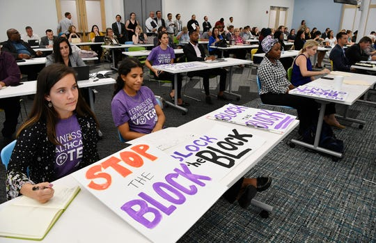 People from the Tennessee Justice Center hold signs at a public hearing Tuesday, Oct. 1, 2019, in Nashville on Tennessee's request for block grant funding for Medicaid.