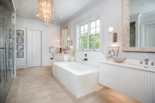Luna Custom Homes' master bath features a large soaking tub surrounded by a quartz surface. The floor is natural limestone tile, and the bath has his-and-her water closets.