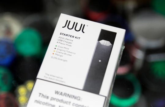 FILE - This Thursday, Dec. 20, 2018 file photo shows a Juul electronic cigarette starter kit at a smoke shop in New York. According to letters released on Friday, Feb. 8, 2019, the head of the Food and Drug Administration is questioning whether electronic cigarette maker Juul and its new partner Altria are following through on pledges to help reverse the current epidemic of underage vaping. (AP Photo/Seth Wenig)