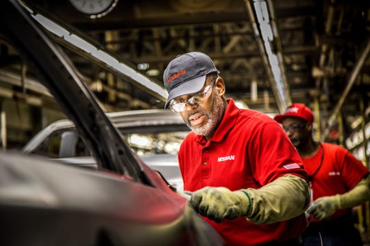 A Nissan manufacturing team member works on the assembly line at the plant in Smyrna.
