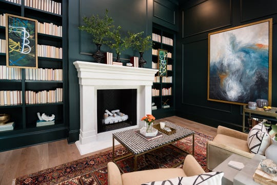 The study in Legend Homes' house features dark blue paneling and draperies. The fireplace is ArcusStone.