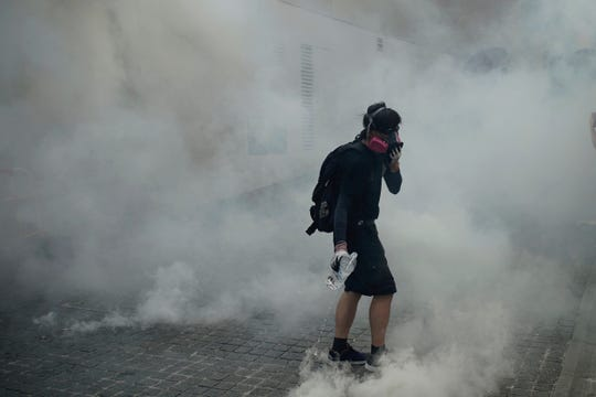 "An anti-government protester walks through tear gas smoke during a clash with police at the Wong Tai Sin area in Hong Kong, Tuesday, Oct. 1, 2019. Thousands of black-clad pro-democracy protesters defied a police ban and marched in central Hong Kong on Tuesday, urging China's Communist Party to ""return power to the people"" as the party celebrated its 70th year of rule. (AP Photo/Felipe Dana )"